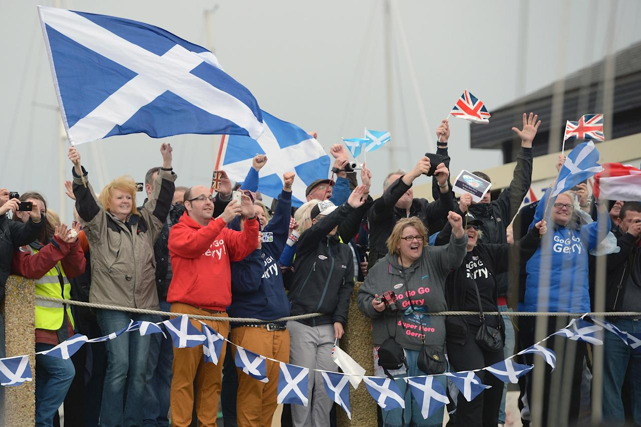TROON, SCOTLAND - MAY 08: Members of the public greet Gerry Hughes as he finishes sailing his yacht Quest III back into Troon Marina on May 8, 2013 in Troon,Scotland. The 55 year old sailor from Glasgow is the first deaf person to sail single handed around the world, he was greeted back in Scotland by a crowd of  around 300 people.  (Photo by Jeff J Mitchell/Getty Images)
