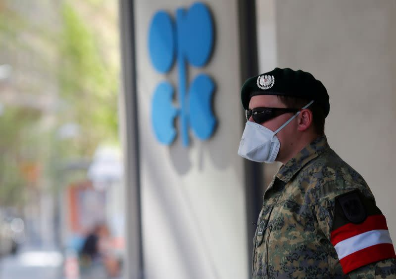 An Austrian army member stands next to the OPEC logo in front of their headquarters in Vienna