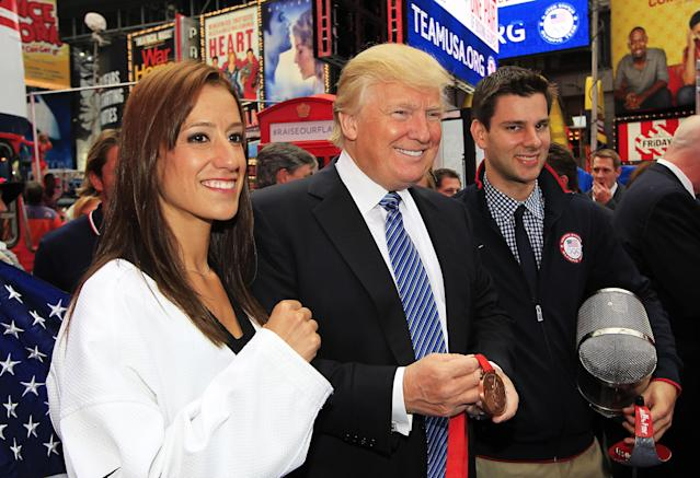 NEW YORK, NY - APRIL 18: Donald Trump poses for a photo with Taekwando athlete Diana Lopez and fencer Tim Morehouse (R) during the Team USA Road to London 100 Days Out Celebration in Times Square on April 18, 2012 in New York City. (Photo by Chris Trotman/Getty Images for USOC)