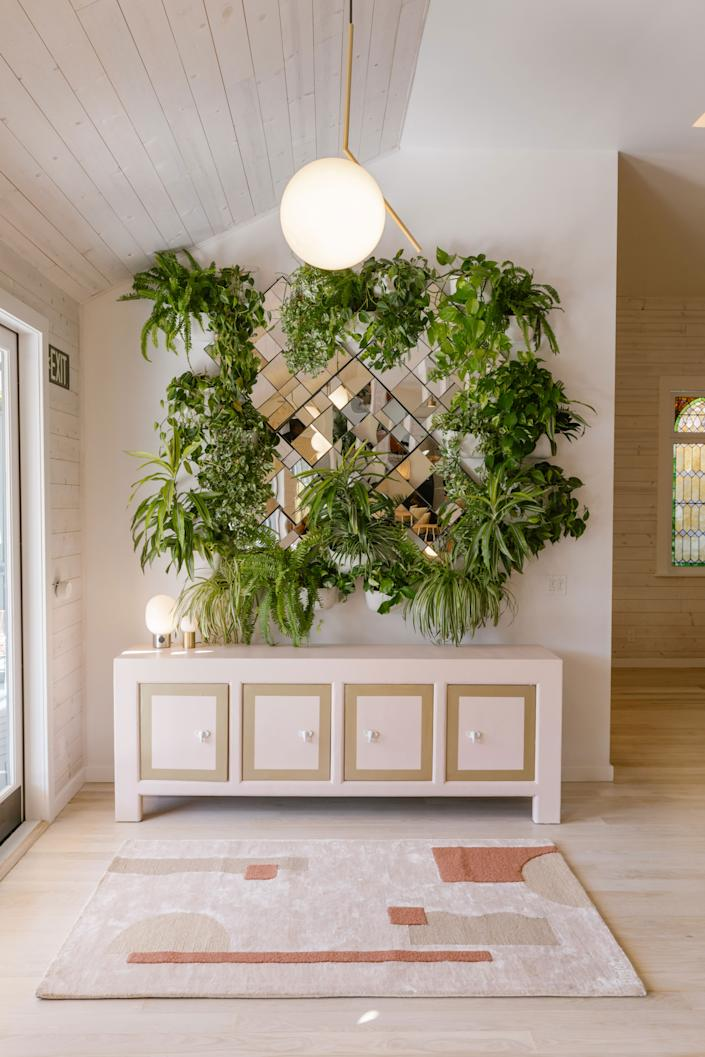 "<div class=""caption""> This large mirror is surrounded by a vertical planting system from the Kansas City–based company <a href=""https://wallygro.com/"" rel=""nofollow noopener"" target=""_blank"" data-ylk=""slk:WallyGro"" class=""link rapid-noclick-resp"">WallyGro</a>. </div>"