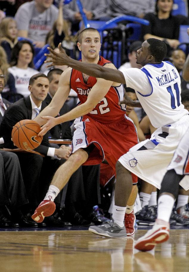Duquesne's Micah Mason (22) passes around Saint Louis' Mike McCall Jr. (11) during the second half of an NCAA college basketball game, Thursday, Feb. 27, 2014 in St. Louis. Mason led all scorers with 22 points as Duquesne defeated Saint Louis 71-64. (AP Photo/Tom Gannam)