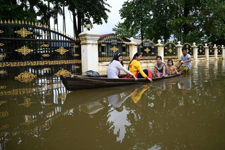 Residents ride in a boat through flooded streets in Shwegyin township in the Bago Region of Myanmar (AFP Photo/Ye Aung THU)