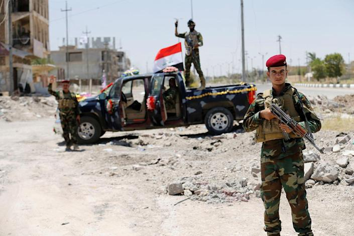 <p>Iraqi government forces react to the camera in Fallujah after government forces recaptured the city from Islamic State militants, Iraq, July 1, 2016. (Photo: Thaier Al-Sudani/REUTERS) </p>
