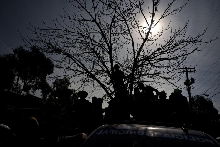 Immigrants, part of the Central American caravan, look at a man that has been detained and placed in a police wagon for, according to the police, smoking marijuana, in Tijuana, Mexico, Wednesday, Nov. 21, 2018. Migrants camped in Tijuana after traveling in a caravan reach the US are weighing their options after a US court blocked President Donald Trump's asylum for illegal border crossers. (AP Photo / Ramon Espinosa)