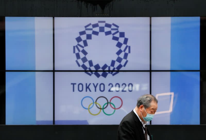 FILE PHOTO: A passerby wearing a protective face mask walks past a screen showing the logo of the Tokyo 2020 Olympic Games in Tokyo