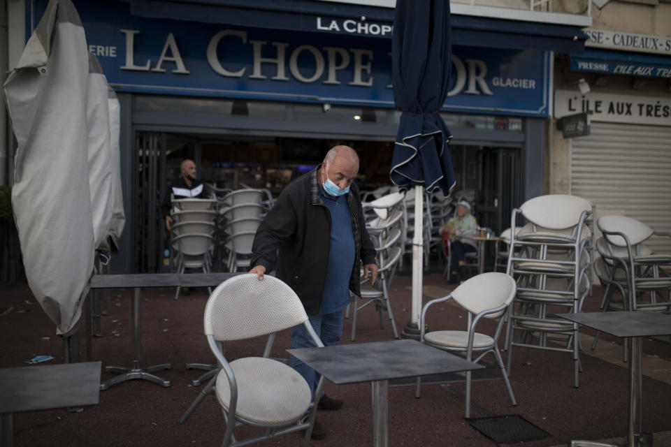 Marc Magere closes his restaurant in Marseille, southern France, Sunday Sept. 27, 2020. As restaurants and bars in Marseille prepared Sunday to shut down for a week as part of scattered new French virus restrictions, Health Minister Olivier Veran insisted that the country plans no fresh lockdowns. (AP Photo/Daniel Cole)