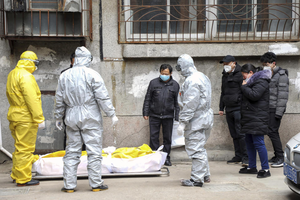 FILE - In this Feb. 1, 2020, file photo, funeral home workers remove the body of a person suspect to have died from a virus outbreak from a residential building in Wuhan in central China's Hubei Province. The Chinese city of Wuhan is looking back on a year since it was placed under a 76-day lockdown beginning Jan. 23, 2020. (Chinatopix via AP, File)