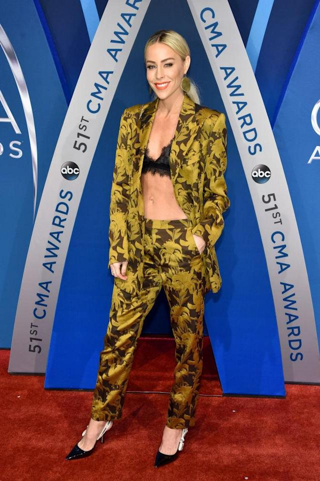<p>The blogger behind Happily Grey wears a black lace bra under a mustard printed suit. (Photo: Getty Images) </p>