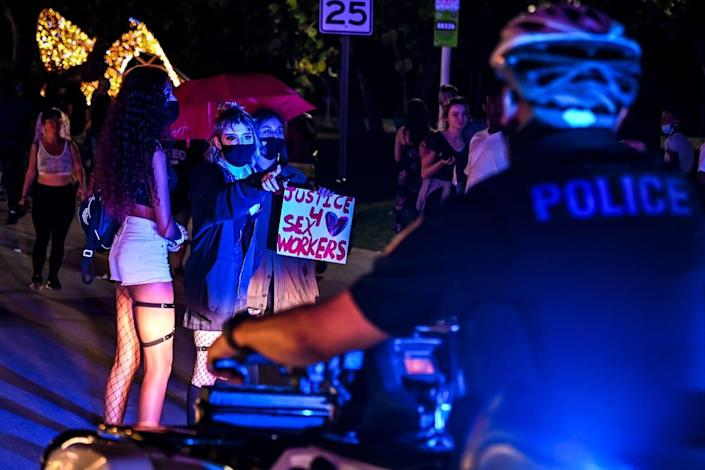 """<div class=""""inline-image__caption""""><p>Activists and sex workers hold up signs near police as they protest for the decriminalization of sex work in Miami Beach, Florida, on December 5, 2020.</p></div> <div class=""""inline-image__credit"""">Chandan Khanna/AFP/Getty</div>"""