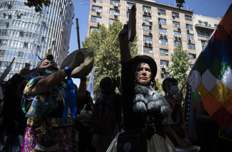 Mapuche and Aymara Indigenous women hold up musical instruments as they shout slogans against police during a protest marking International Women's Day in Santiago, Chile, Monday, March 8, 2021. (AP Photo/Esteban Felix)