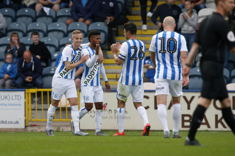 ROCHDALE, ENGLAND - JULY 17: Elias Kachunga scores and is congratulated by Huddersfield team mates Florent Hadergjonaj, Christopher Schindler, and Aaron Mooy during the game between Rochdale and Huddersfield Town at the Crown Oil Arena on July 17, 2019 in Rochdale, England. (Photo by John Early/Getty Images)