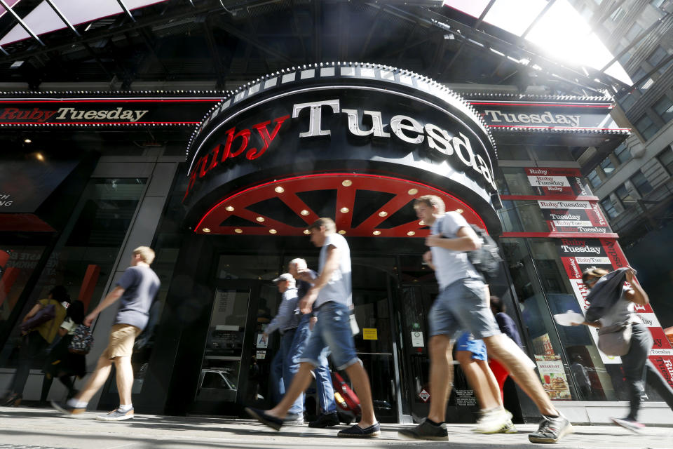FILE - In this Sept. 16, 2016 file photo, visitors to New York's Times square walk past a Ruby Tuesday restaurant.  Ruby Tuesday is filing for bankruptcy protection, the latest casual chain to suffer from coronavirus-related closures and changing consumer habits. The Maryville, Tennessee-based company says, Wednesday, Oct. 7, 2020 its restaurants will remain open throughout the bankruptcy process.  (AP Photo/Mary Altaffer, File)