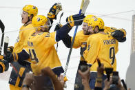 Nashville Predators center Luke Kunin, second from right, celebrates with Mattias Ekholm (14) and Filip Forsberg (9) after Kunin scored the winning goal against the Carolina Hurricanes during the second overtime in Game 4 of an NHL hockey Stanley Cup first-round playoff series Sunday, May 23, 2021, in Nashville, Tenn. The Predators won 4-3 to even the series 2-2. (AP Photo/Mark Humphrey)