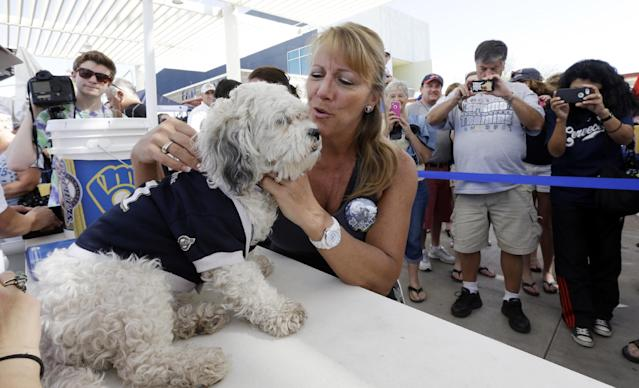 FILE - In this March 15, 2014 file photo, the Milwaukee Brewers unofficial mascot Hank the Dog is photographed with fans during an exhibition spring training baseball game against the Cincinnati Reds, in Phoenix. (AP Photo/Morry Gash)