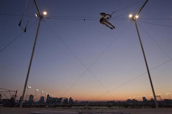 A woman practices on a trapeze shortly after sunset at Trapeze School New York July 1, 2012.
