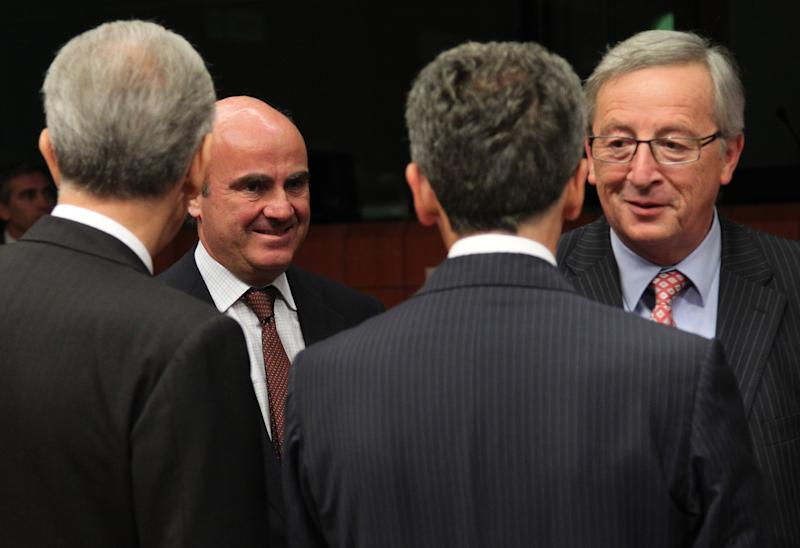 Spanish Finance Minister Luis de Guindos Jurado, second left, and Chairman of the Eurogroup and Luxembourg's Prime Minister Jean-Claude Juncker, right, arrive at the Eurogroup ministerial meeting at the European Council building in Brussels, Monday, July 9, 2012. European finance ministers are to use this week's meetings in Brussels to attempt to secure Spain's teetering economy, with progress expected on the bailout loan for the country's stricken banks and a relaxation of the government's financial targets. (AP Photo/Yves Logghe)