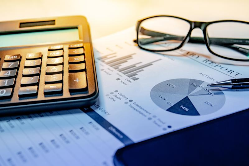 Calculator, eyeglasses, pen, smartphone and summary report paperwork with bar graph, pie chart and table. Financial data analysis. Business planning and management concept