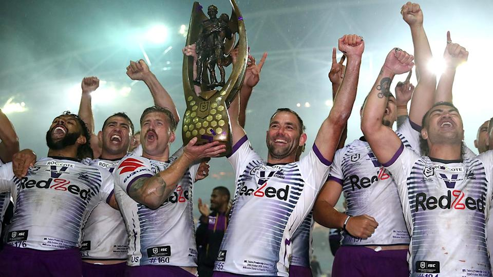 Melbourne Storm players, pictured here celebrating with the NRL premiership trophy.