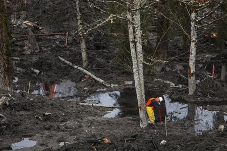 A rescue worker takes a break while working in a debris field left by a mudslide in Oso