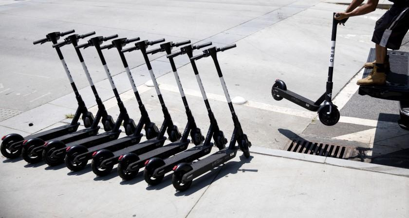 """James Wilson lines up electric scooters on a street corner after charging them overnight in Atlanta, Friday, June 28, 2019. """"It's a good little side hustle,"""" said Wilson who has found greater fortune in charging the scooters than his old job of driving a truck. Supporters of the scooters, which have popped up in cities across the country, say they're great for short trips, but critics say they're a nuisance and can be dangerous to their drivers, pedestrians and motorists. (AP Photo/David Goldman)"""