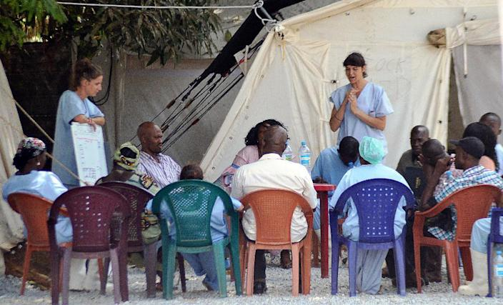 Health workers speak to relatives of people infected with Ebola at an isolation center at Donka Hospital in Conakry on April 14, 2014 (AFP Photo/Cellou Binani)
