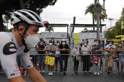 People wear masks as they watch riders prior to the start of the first stage of the Tour de France cycling race over 156 kilometers (97 miles) with start and finish in Nice, southern France, Saturday, Aug. 29, 2020. (AP Photo/Christophe Ena)