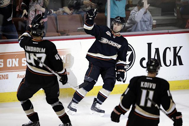 Anaheim Ducks' Andrew Cogliano, center, celebrates his goal with Hampus Lindholm, left, of Sweden, during the first period of an NHL hockey game against the Vancouver Canucks on Wednesday, Jan. 15, 2014, in Anaheim, Calif. (AP Photo/Jae C. Hong)