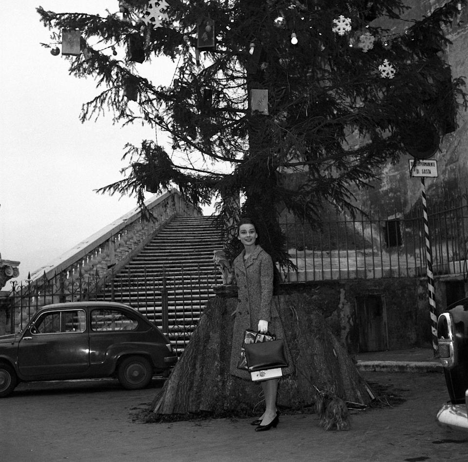<p>The <em>Breakfast at Tiffany's</em> star stands in front of a large Christmas tree in Rome, 1950.</p>