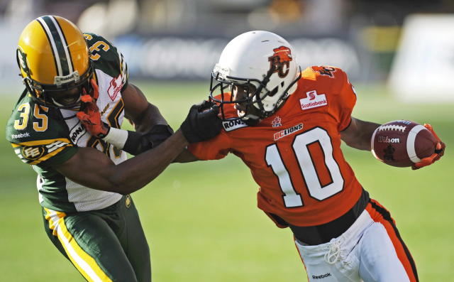 Edmonton Eskimos' Weldon Brown, left, collects a penalty for grabbing the face mask of B.C. Lions' Kierrie Johnson during first quarter CFL pre-season football action in Edmonton, Alta., Thursday, June 21, 2012. THE CANADIAN PRESS/John Ulan
