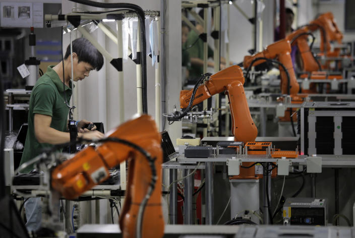 In this Aug. 21, 2015 photo, a Chinese man works amid orange robot arms at Rapoo Technology factory in southern Chinese industrial boomtown of Shenzhen. Factories in China are rapidly replacing those workers with automation, a pivot that's encouraged by rising wages and new official directives aimed at helping the country move away from low-cost manufacturing as the supply of young, pliant workers shrinks. (AP Photo/Vincent Yu)