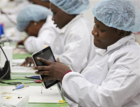 Workers assemble Android-based tablets from imported components at the Surtab factory in the Sonapi Industrial Park of Port-au-Prince March 11, 2014. REUTERS/Marie Arago