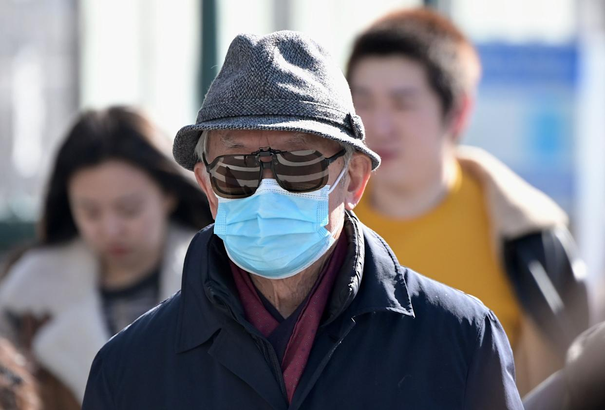 """People wear surgical masks in fear of the coronavirus in Flushing, a neighborhood in the New York City borough of Queens on February 3, 2020. - China's top leadership on Monday admitted """"shortcomings and difficulties"""" in its response to the coronavirus outbreak and the government said it """"urgently"""" needed medical supplies to battle the outbreak which has killed more than 360 people.The virus has since spread to more than 20 countries despite many governments imposing unprecedented travel bans on arrivals coming from China. (Photo by Johannes EISELE / AFP) (Photo by JOHANNES EISELE/AFP via Getty Images)"""