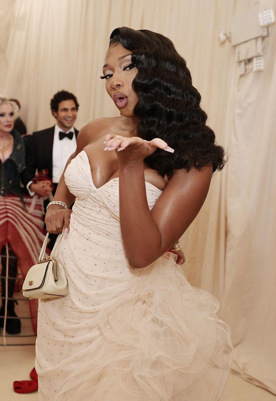 <p>The queen of hair switch-ups walked the red carpet with voluminous Hollywood waves that were swept to the side. She kept her makeup muted and neutral with soft nudes and mauves on the lips and eyes.</p>
