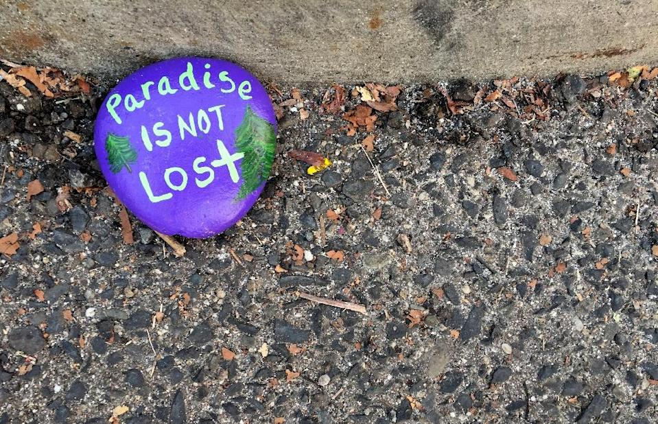 A painted rock on the ground of the parking lot bears a phrase of optimism over the town of Paradise, which was largely destroyed by the fire (AFP Photo/Javier TOVAR)