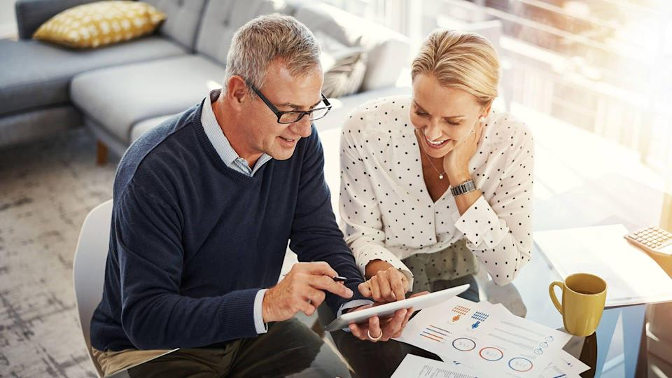 Shot of a mature couple using a digital tablet while going through paperwork at home.