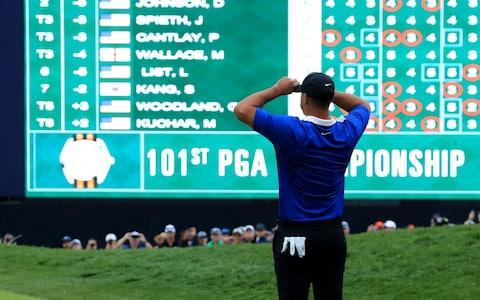 Brooks Koepka of the United States looks at the scoreboard after holing the winning putt to secure his one shot win in the final round - Credit: David Cannon/GETTY IMAGES