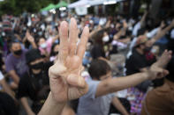 Pro-democracy activists flash three-fingered salutes outside remand prison, in which some of the activists are kept in Bangkok, Thailand, Friday, Oct. 23, 2020. Thailand's government on Thursday canceled a state of emergency it had declared last week for Bangkok in a gesture offered by the embattled prime minister to cool student-led protests seeking democracy reforms. (AP Photo/Sakchai Lalit)