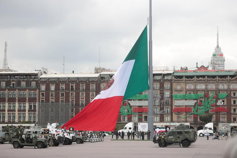 VARIOUS CITIES, MEXICO - SEPTEMBER 16: The mexican flag is hoisted during the Independence Day military parade at Zocalo Square on September 16, 2020 in Various Cities, Mexico. This year El Zocalo remains closed for general public due to coronavirus restrictions. Every September 16 Mexico celebrates the beginning of the revolution uprising of 1810. (Photo by Hector Vivas/Getty Images)