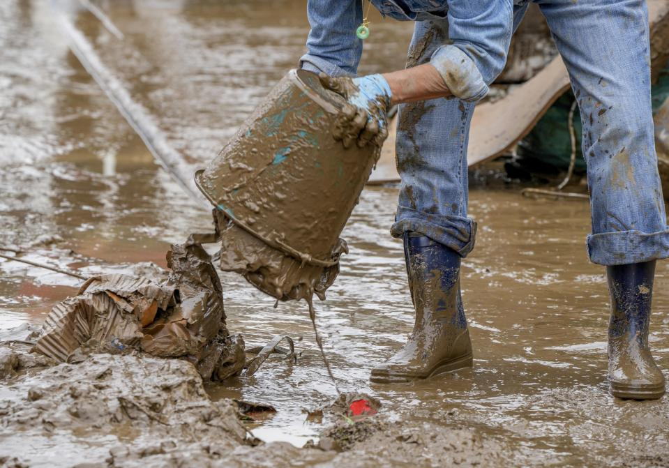 A person cleans mud from their home in Bad Neuenahr-Ahrweiler, Germany, Saturday, July 17, 2021. Due to strong rainfall, the Ahr river went over its banks and flooded big parts of the town. (AP Photo/Michael Probst)