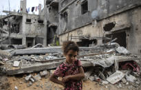 Palestinian Rahaf Nuseir, 10, looks on as she stands in front of her family's destroyed homes, to which they returned following a cease-fire reached after an 11-day war between Gaza's Hamas rulers and Israel, in town of Beit Hanoun, northern Gaza Strip, Friday, May 21, 2021. (AP Photo/Khalil Hamra)