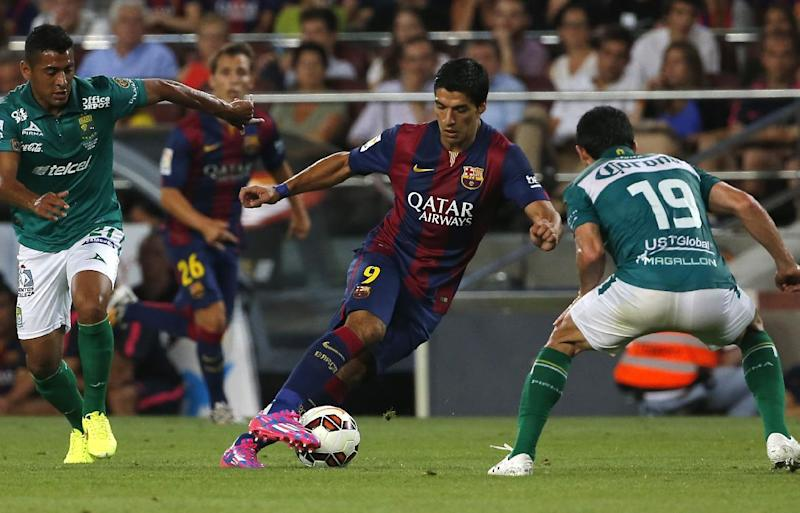 Barcelona's Luis Suarez from Uruguay fights for the ball against Leon's Luis Antonio Delgado, left, and Jonny Magallon, during the Joan Gamper trophy friendly soccer match between Barcelona and Leon at the Camp Nou stadium in Barcelona, Spain, Monday, Aug. 18, 2014