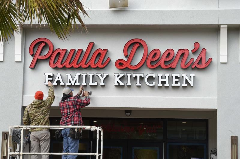CORRECTS SPELLING OF DEEN - Ryder Kenney, left, and Robert Litzenberger, owner of Destin Sign Company, remove the sign outside of Paula Deen's Family Kitchen restaurant at Destin Commons Tuesday, Nov 12, 2019, in Destin, Fla. The restaurant which opened in March 2019, was abruptly closed Monday along with a similar new Paula Deen's Family Kitchen restaurant in Panama City Beach, Fla. (Devon Ravine/Northwest Florida Daily News via AP)