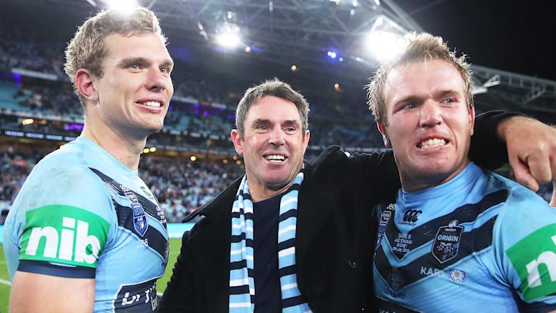 Blues coach Brad Fittler hugs and celebrates with Tom Trbojevic and Jake Trbojevic.