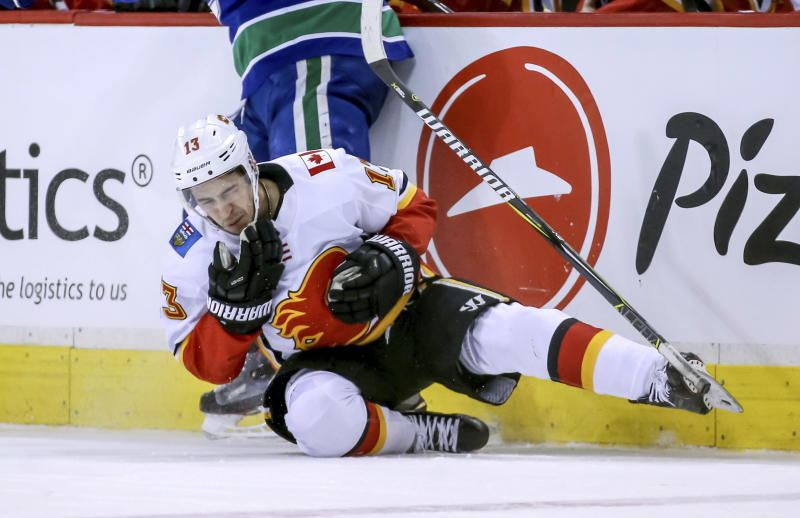 Calgary Flames' Johnny Gaudreau (13) falls to the ice after being high-sticked by Vancouver Canucks' Bo Horvat during the second period of an NHL hockey game Saturday, March 23, 2019, in Vancouver, British Columbia. (Ben Nelms/The Canadian Press via AP)