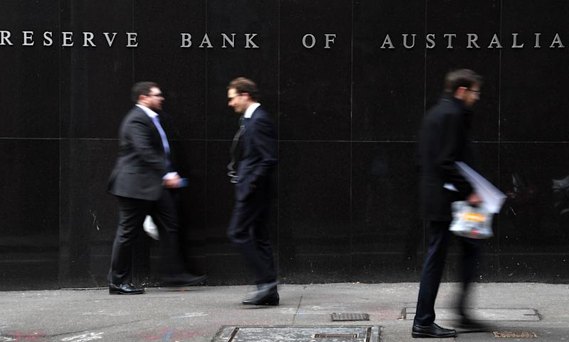 Office employees walk in front of the Reserve Bank of Australia in Sydney on September 4, 2018. - Weak inflation, sluggish wage growth and high levels of household debt saw Australia's central bank keep interest rates on hold at a record low on September 4. (Photo by Saeed KHAN / AFP) (Photo credit should read SAEED KHAN/AFP/Getty Images)