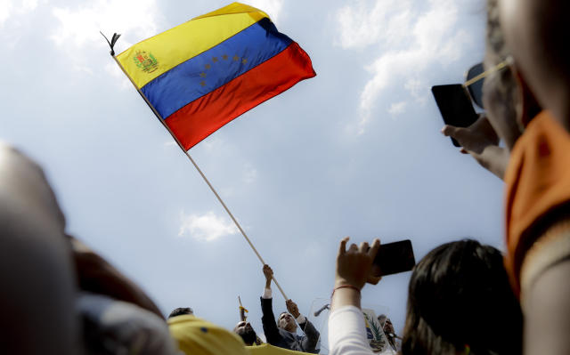Venezuelan opposition leader Juan Guaido, who has declared himself interim president, holds a national flag during a rally in Valencia, Venezuela, Saturday, March 16, 2019. Large crowds gathered in the northern Venezuelan city to greet Guaido, who plans to tour the country as part of his campaign to oust President Nicolas Maduro. (AP Photo/Natacha Pisarenko)