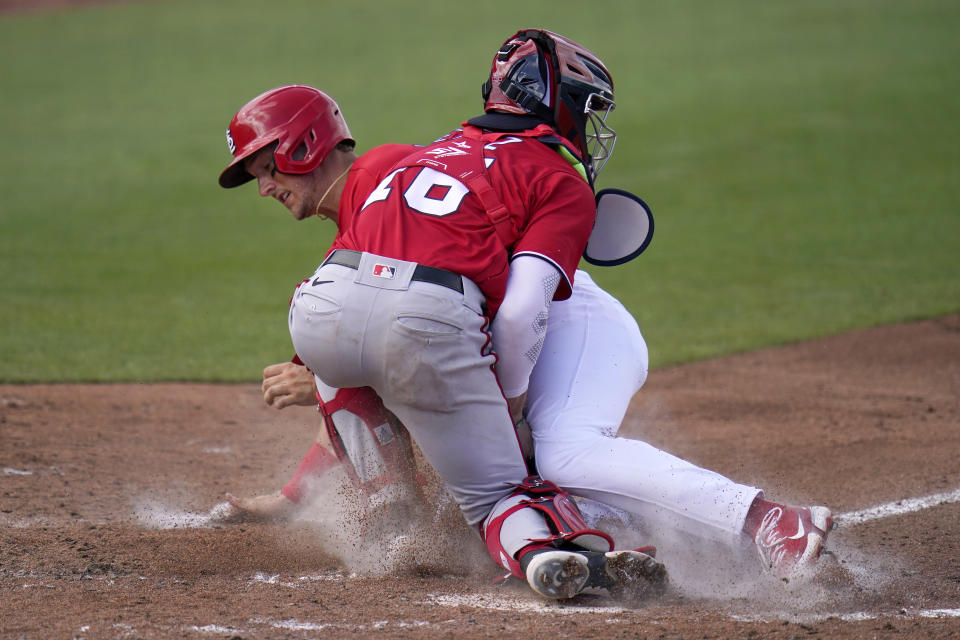 St. Louis Cardinals' Andrew Knizner, rear, is tagged out at home by Washington Nationals catcher Jakson Reetz during the fourth inning of a spring training baseball game Sunday, Feb. 28, 2021, in Jupiter, Fla. (AP Photo/Jeff Roberson)