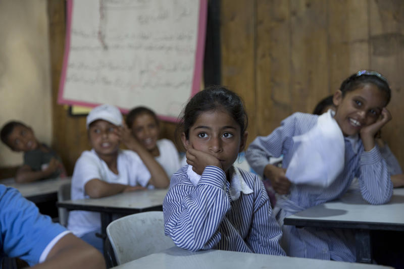 "FILE - In this July 16, 2018 file photo, Palestinians attend school in the West Bank Bedouin community of Khan al-Ahmar. Qatar's Foreign Ministry said Tuesday, May 7, 2019, that it will send $480 million to Palestinians in the West Bank and the Gaza Strip after a cease-fire deal ended the deadliest fighting between Israel and Palestinian factions since a 2014 war. A statement from Qatar said $300 million would support health and education programs of the Palestinian Authority, while $180 million would go toward ""urgent humanitarian relief"" in United Nations programs and toward electricity. (AP Photo/Nasser Nasser, File)"