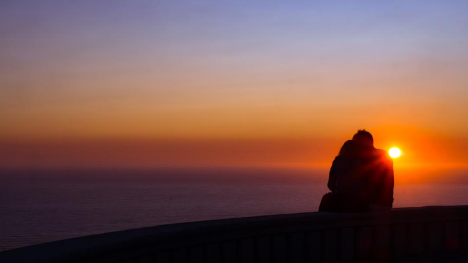 Back view of a couple silhouette watching sun at sunset with the sea at the background at summertime with a warmth light