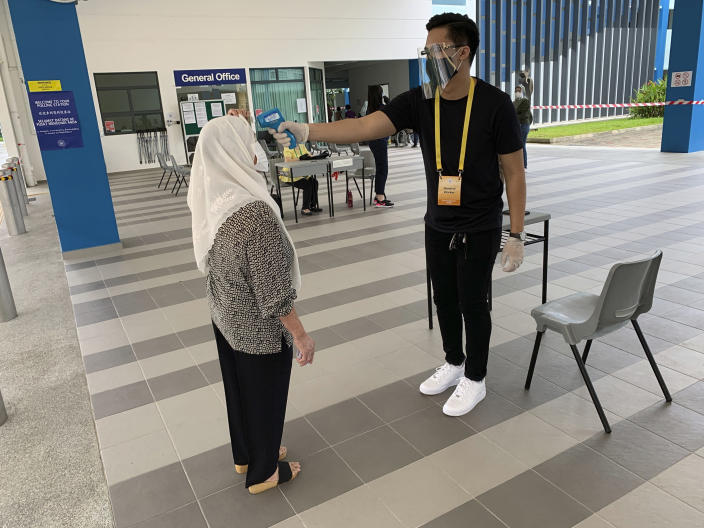 A voter, left, wearing a face mask has her temperature checked with a thermal scanner at the Dunearn Secondary School polling station in Singapore Friday, July 10, 2020. Wearing masks and plastic gloves, Singaporeans began voting in a general election that is expected to return Prime Minister Lee Hsien Loong's long-ruling party to power. (AP Photo/Royston Chan)